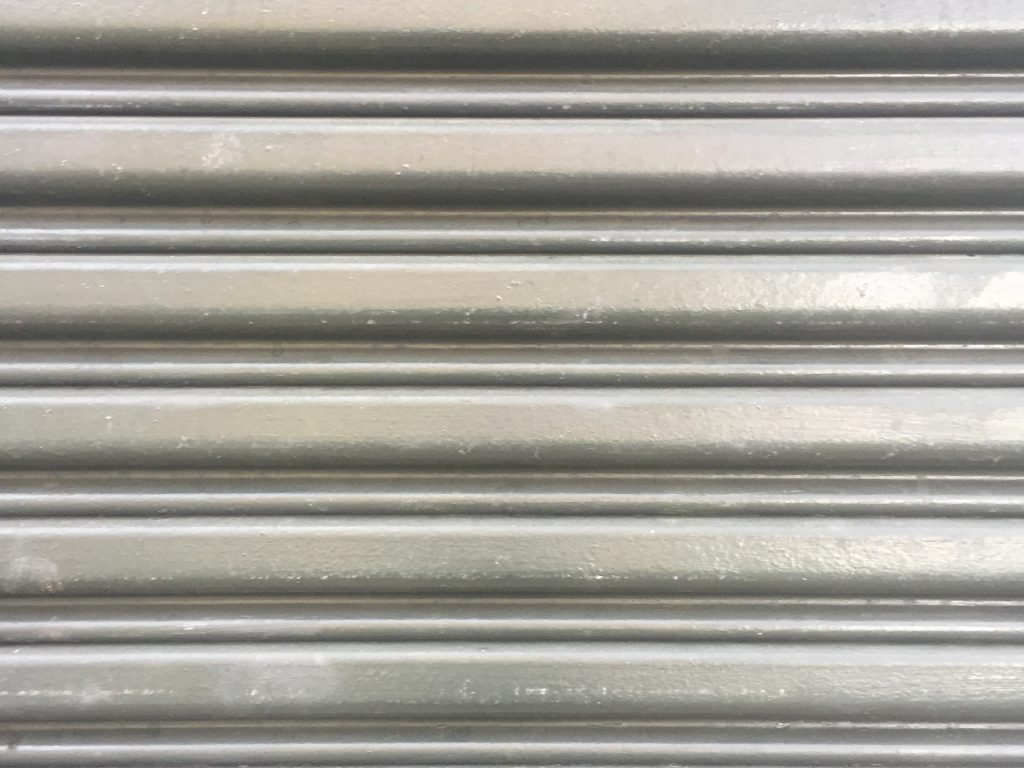 Metal wall with horizontal folds creating pattern of lines