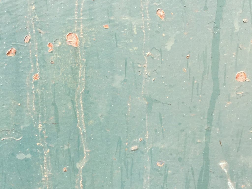 Green paint over corroded and rusty metal