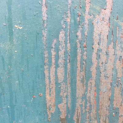 Dirty teal paint over very rusty metal with chips