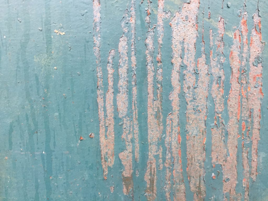 Rust metal with chipped teal paint creating grungy surface