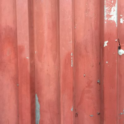 Faded red paint pealing back from metal wall