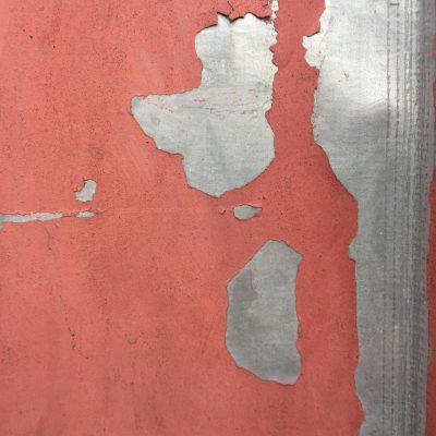 Red paint that is dirty and chipping over metal surface