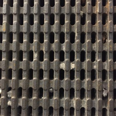 Dark rust brown iron grate with holes