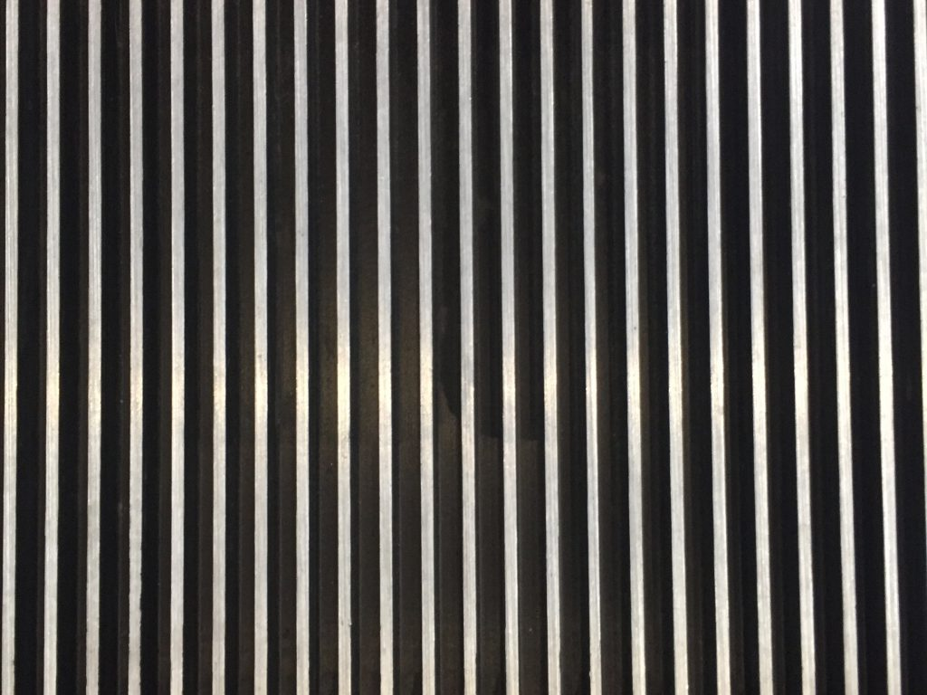 Thick metallic ridges of black and white vertical lines