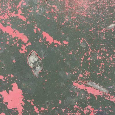 Layers of red and black paint chips on metal surface