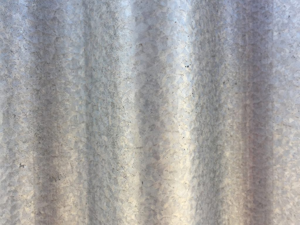 Textured metal wall with ridges featuring silver and glossy edges