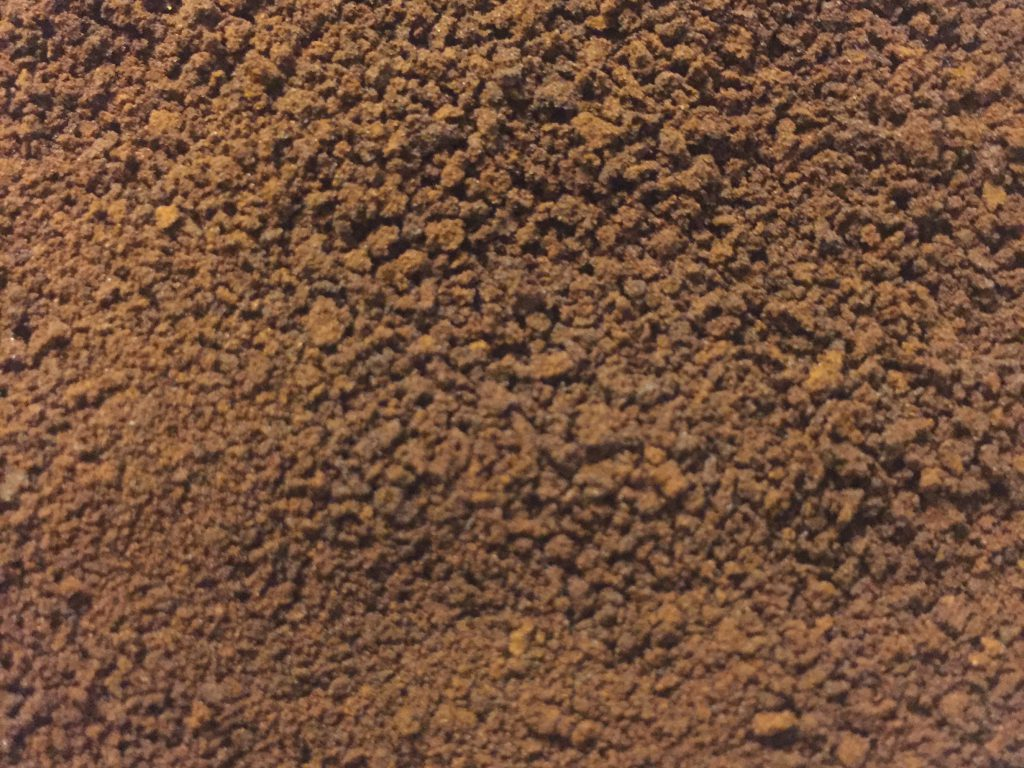 Dark brown coffee grounds close up texture