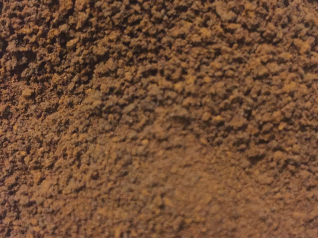Deep brown coffee grounds close up