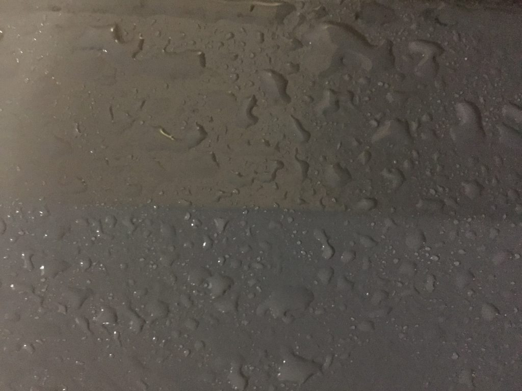 Charcoal grey paint with water drops sitting on top
