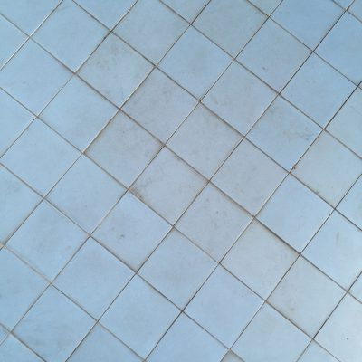 Light blue tiles that are dirty and have some scuffs