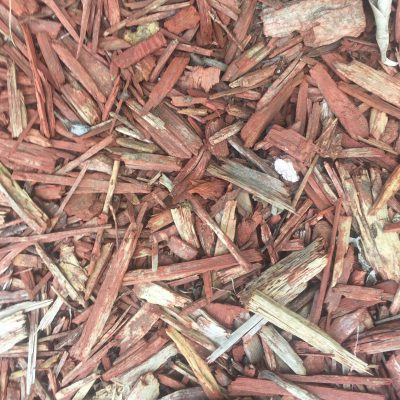 Red and white chunks of wood in mulch bed