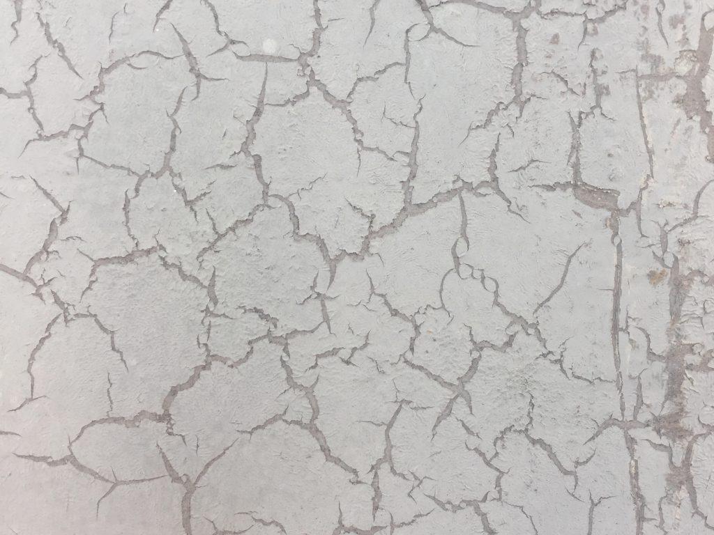 Off white splintering paint on concrete wall