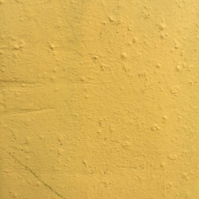 Concrete wall with lots of texture and yellow paint