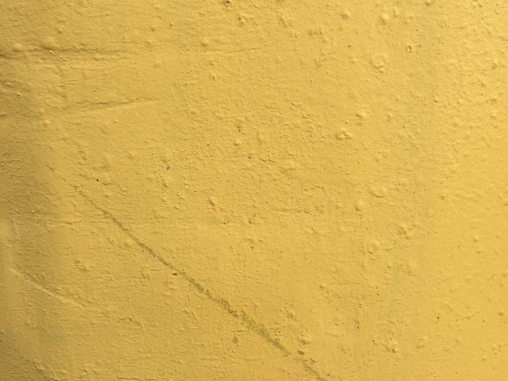 Bright yellow painted wall with lots of texture