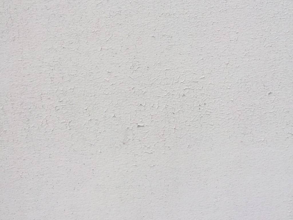 Paint chips on white concrete wall creating nice texture