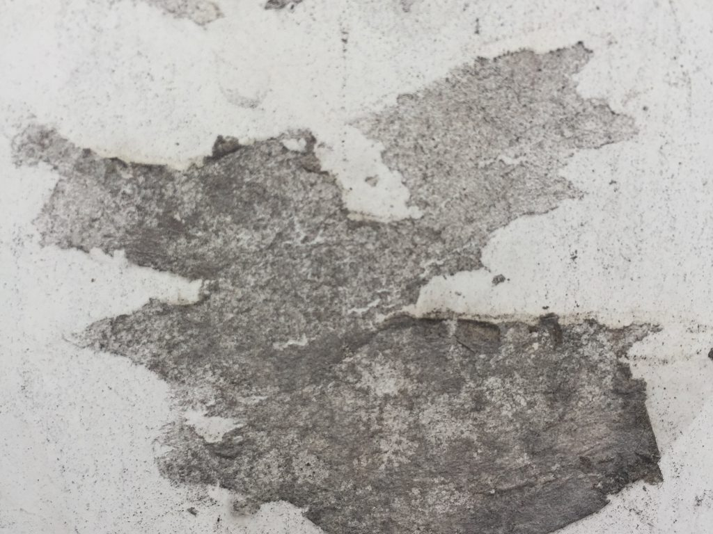 Noisy white wall with black tar smudge in middle