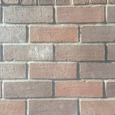 Pattern of bright bricks with alternating shades of red