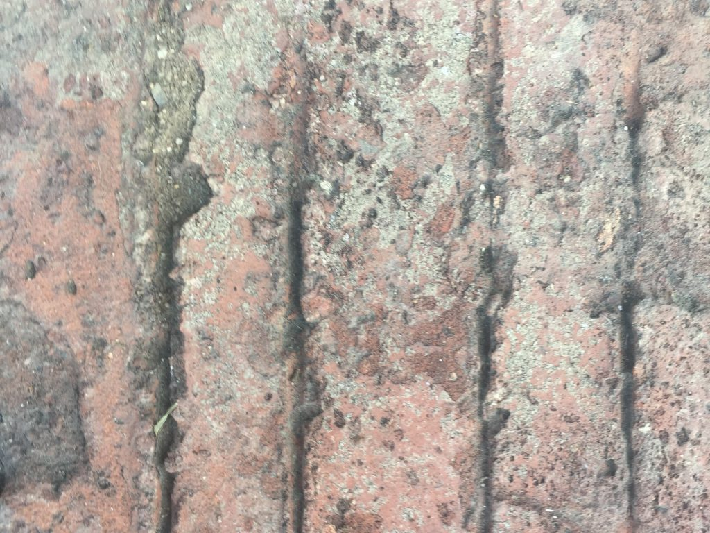 Close up of grungy red brick pavement