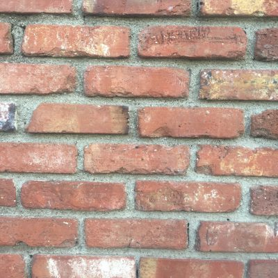Brick wall pattern. Large gaps between bricks filled with concrete.