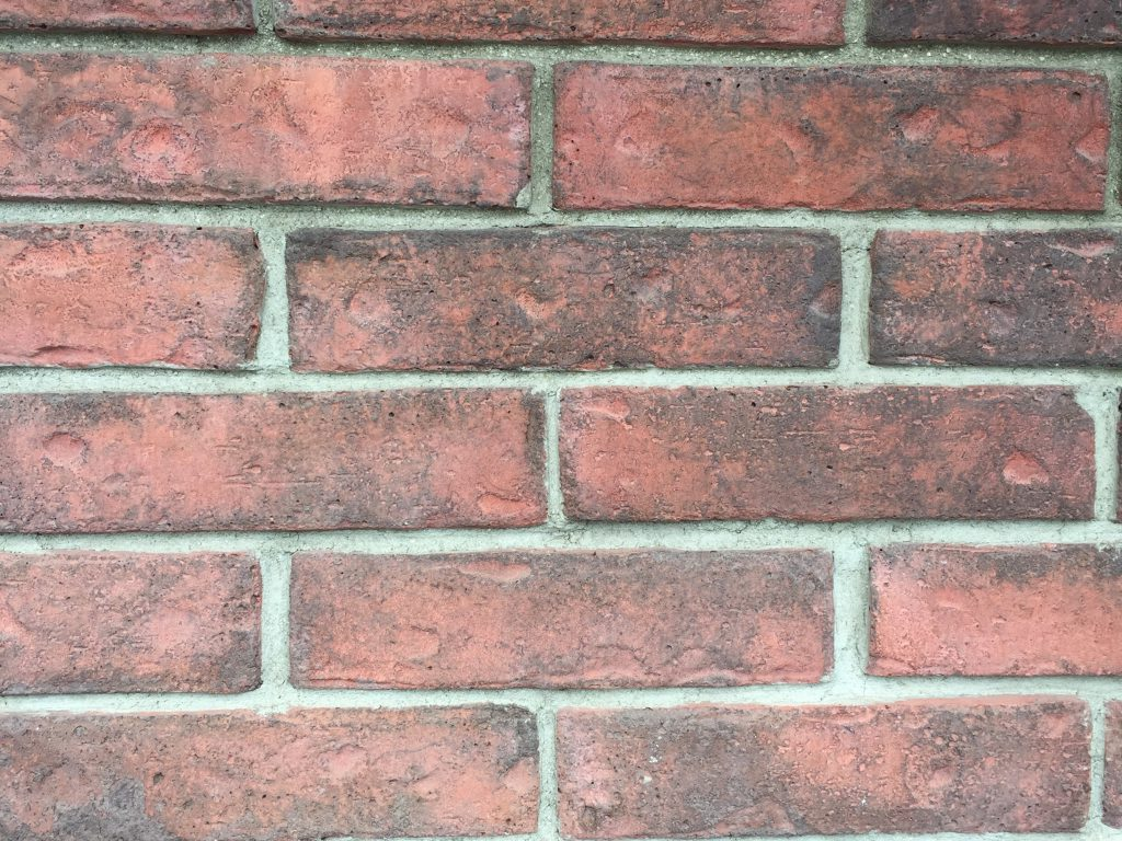 Red brick wall with dark smudges