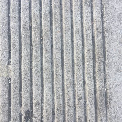 Concrete sidewalk that is dirty and has vertical scores