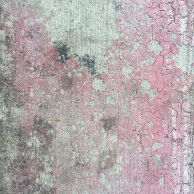 Cracked red paint on dirty concrete street