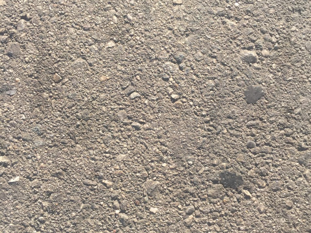 Light grey rough concrete texture with small to large rocks