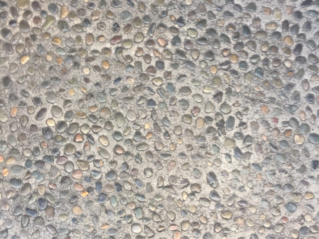 Concrete with colorful pebbles on sidewalk