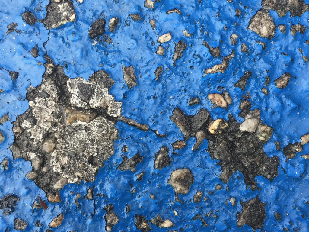 Glossy blue paint melted over weather worn dark grey concrete