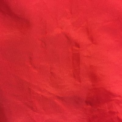 Bold red plastic fabric bag with wrinkles stock texture