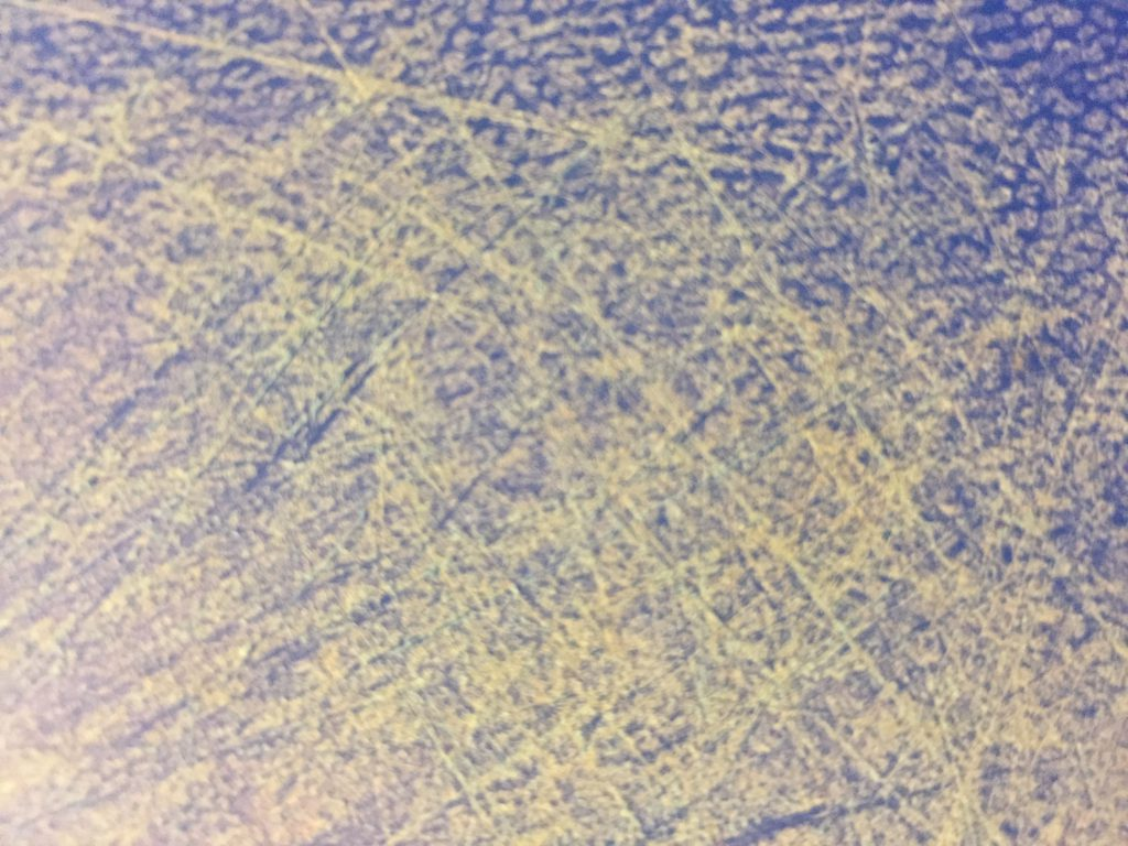 yellow-green scratches all over a blue plastic cutting board