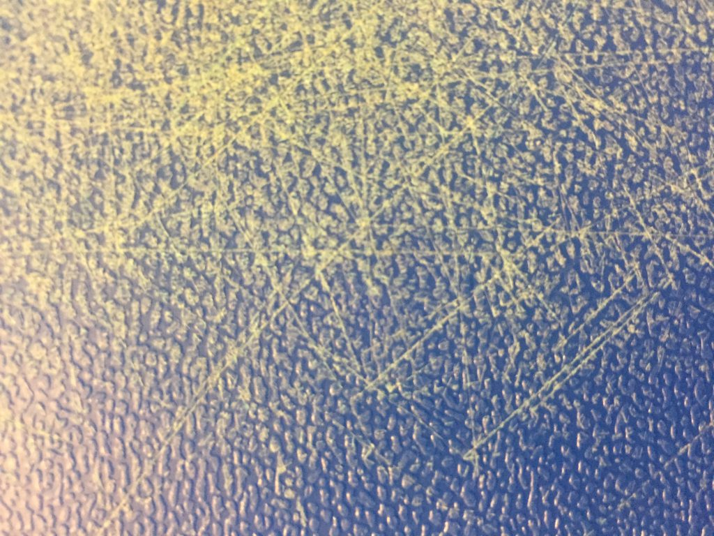 Blue cutting board close up featuring texture and scratches