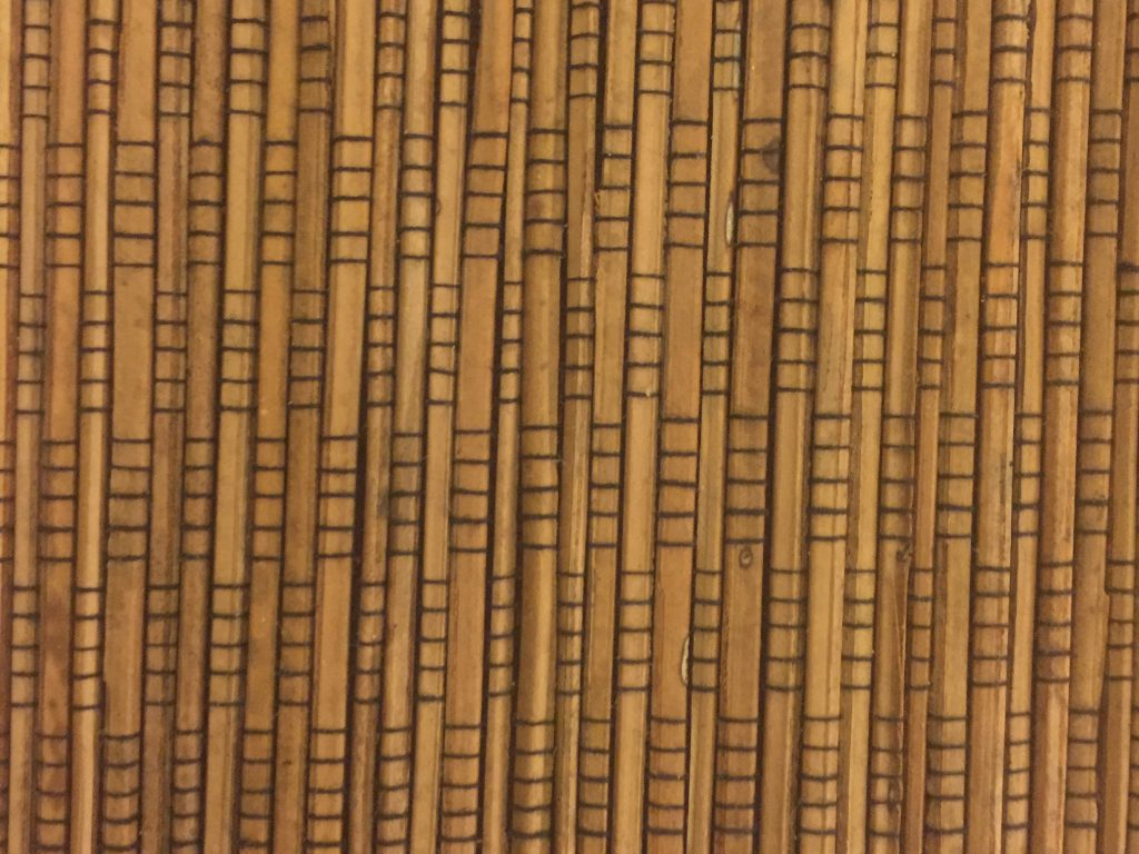Thin wood strips lined up vertically with pattern of scoring lines