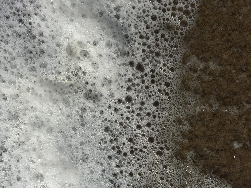 Thick sea foam transitioning into clear water over dark brown sand