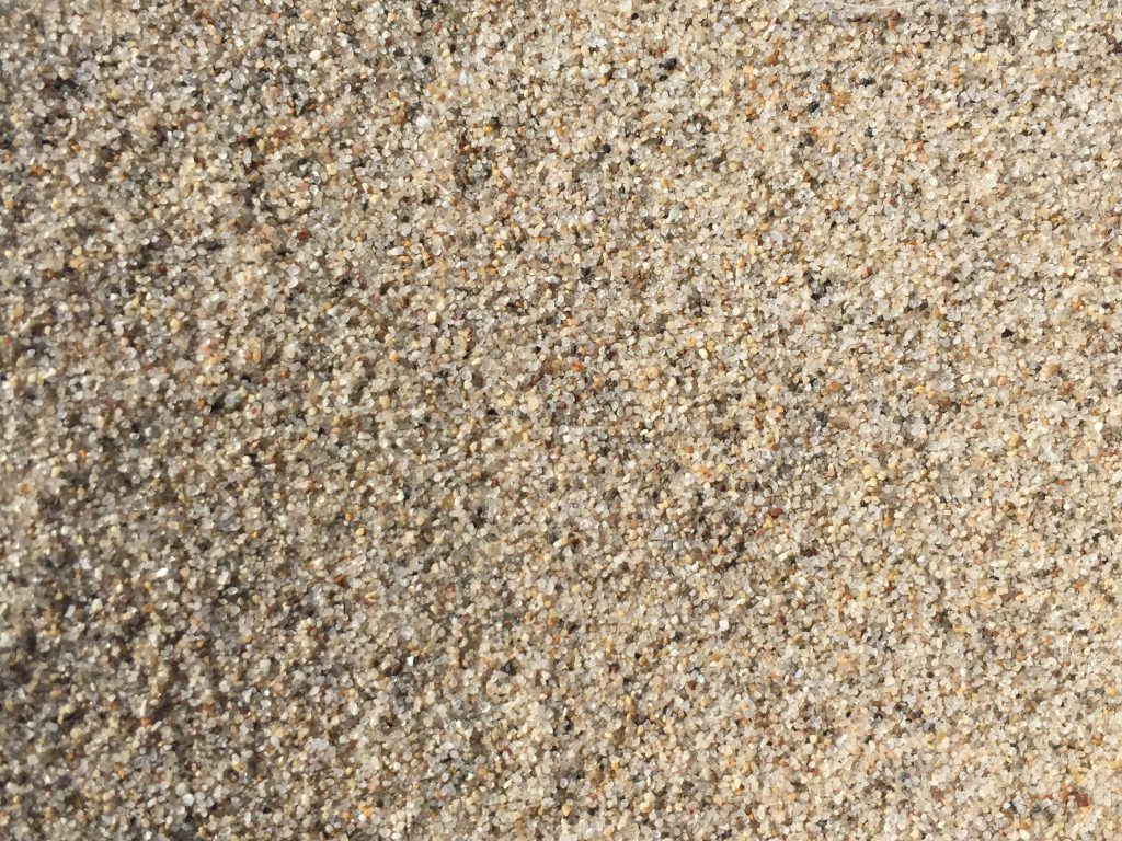 Close up coarse grains of sand with lots of noise