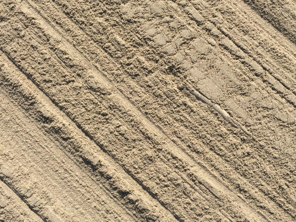 Smooth light brown sand with diagonal brush marks