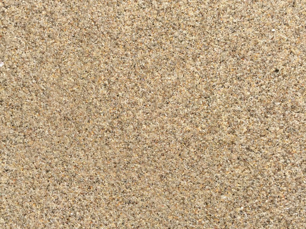 Small bumps in wet sand with speckled texture