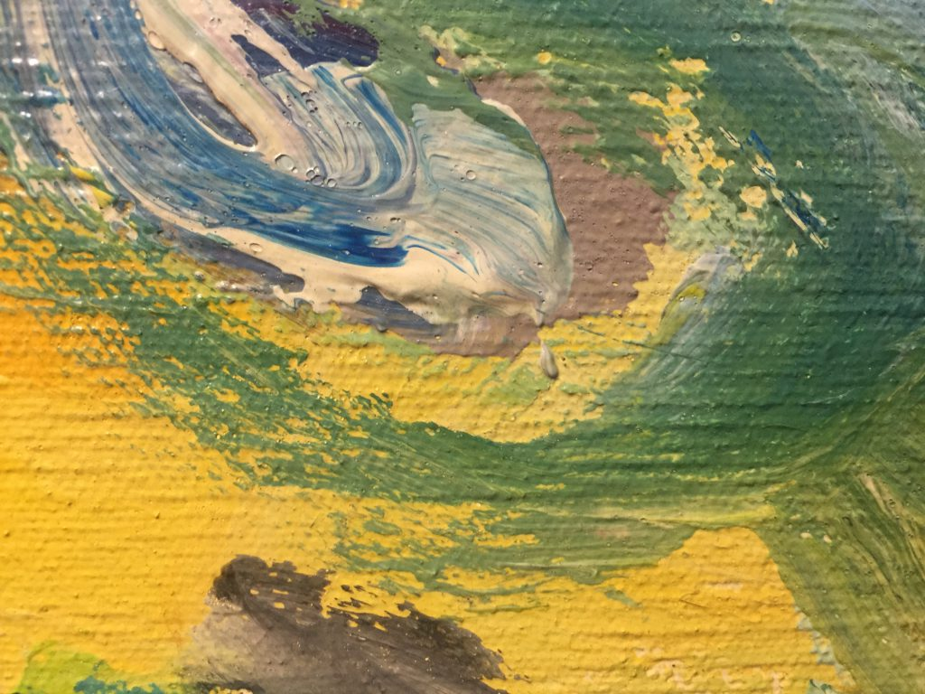 Close up of yellow paint on canvas with variety of brush strokes