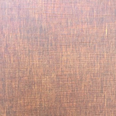 Red brown wood table top with splotches of darker stain