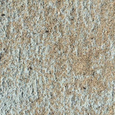 Teal textured surface covered with sand
