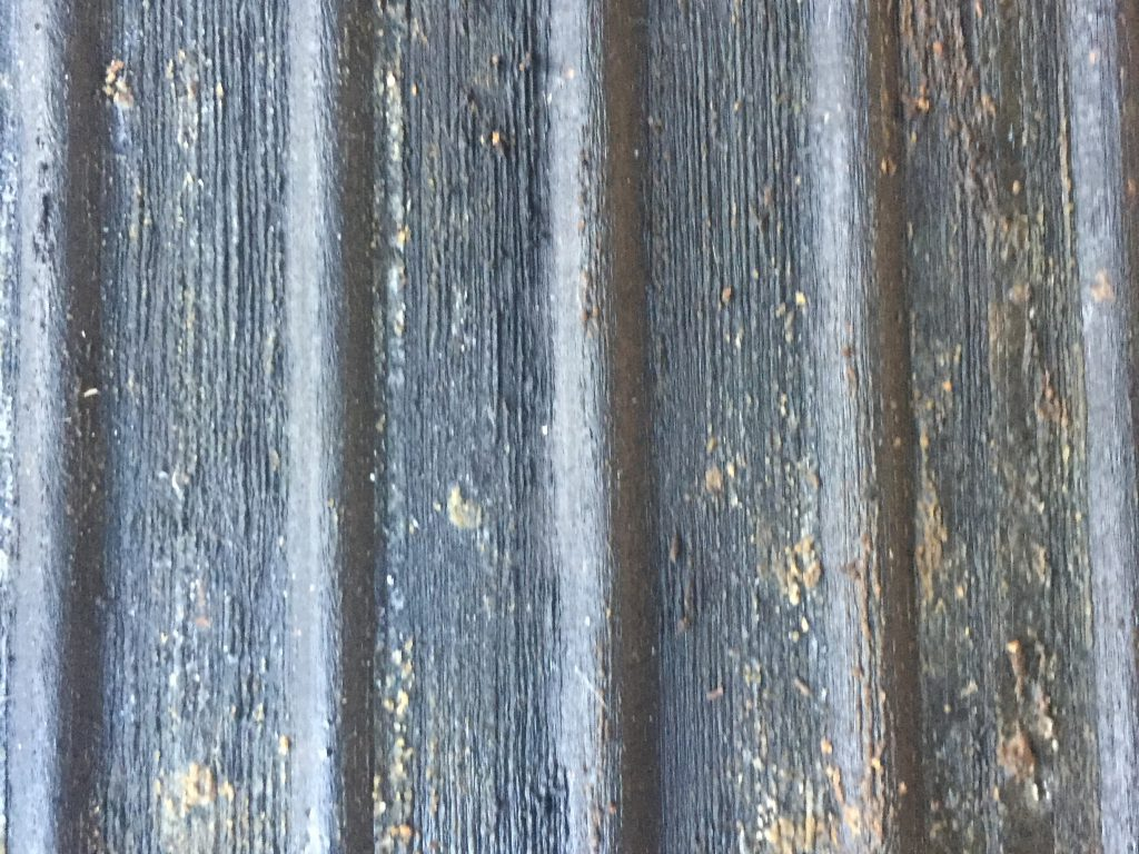 Dark grey metal surface that is dirty and has vertical lines