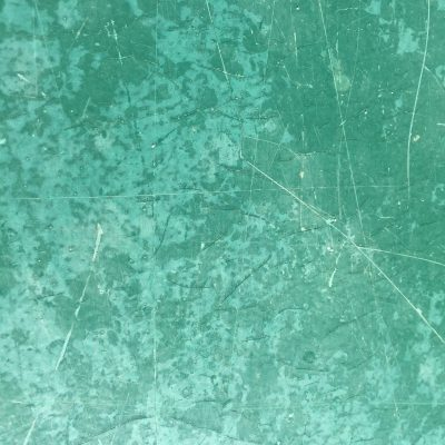 Close up of beat up green surface with lots of scratches