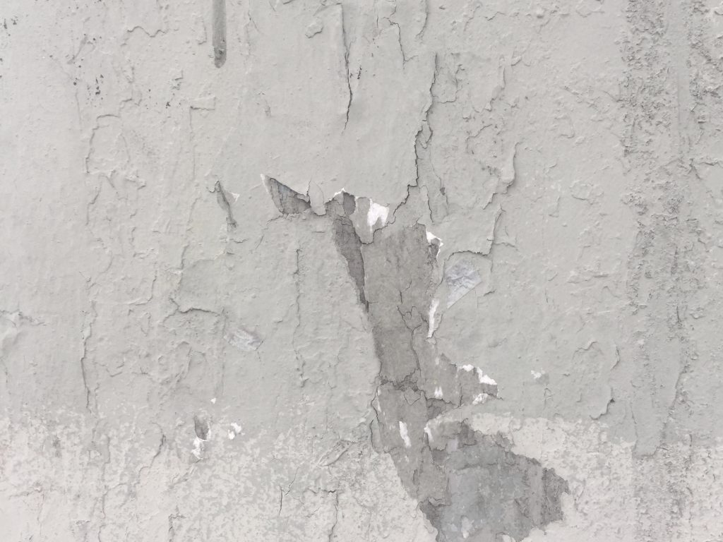 Cracked and dirty concrete wall with chipping white paint