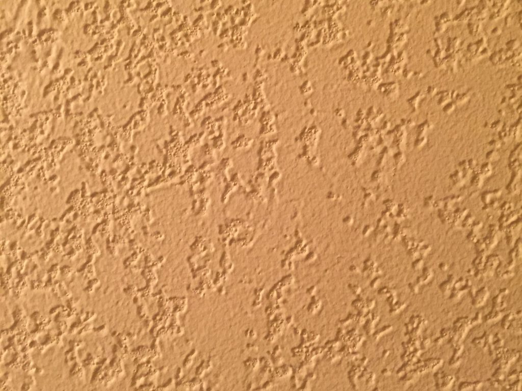 Yellow paint on textured stucco wall