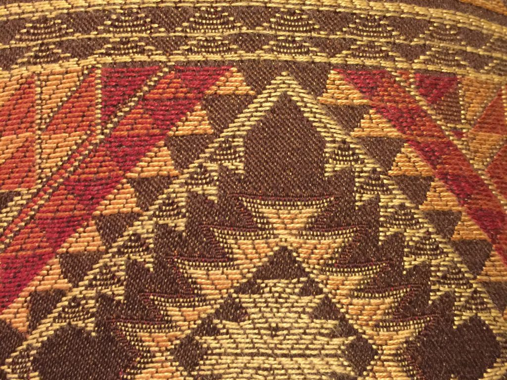 Red brown and beige stitching pattern close up upholstery