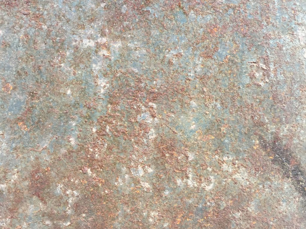 Dark rust covering metal surface with slight corrosion