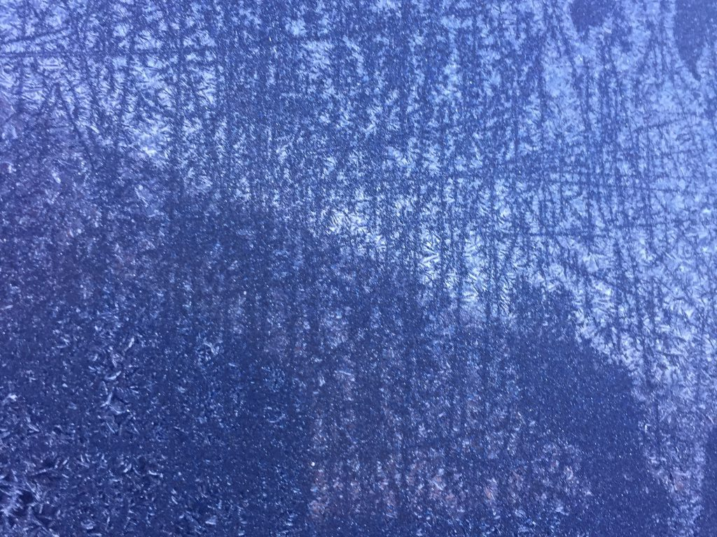 Thin layer of frost over blue window