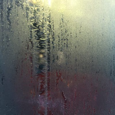 Thin layer of frost over window with yellow blue and red reflections