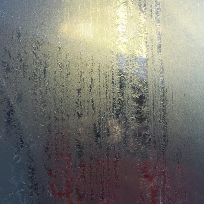Icy frost layer over glass window with vertical streaks