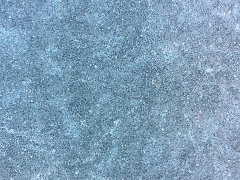 Crystalized patterns of frost over blue surface